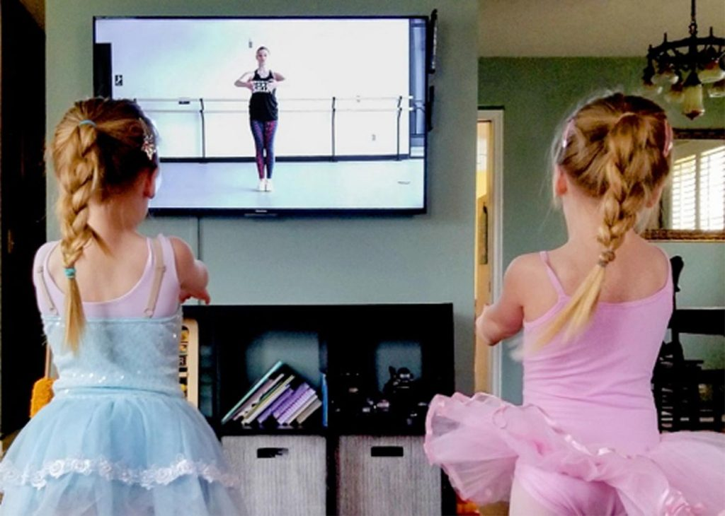 Two young dancers participate in American Midwest Ballet's online dance classes from their living room.